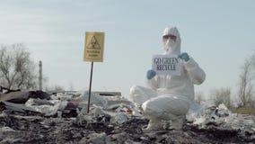De Biohazardnoodsituatie, Hazmat-bioloog in Beschermend Kostuum toont het teken groene kringloop op vuilnisstortplaats met wijzer stock footage