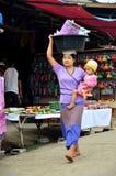 De Birmaanse Moeder houdt de baby en het dragende bassinplastiek op haar h stock foto