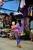 De Birmaanse Moeder houdt de baby en het dragende bassinplastiek op haar h stock fotografie