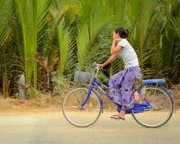 De Birmaanse vrouw berijdt fiets langs plattelandsstraat Stock Foto's
