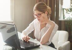 De bisnesswoman zitting in het bureau Stock Afbeeldingen