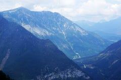De blåa österrikiska bergen i den snövita ogenomskinligheten av moln Royaltyfri Fotografi