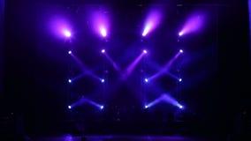 De blåa strålarna som växelvis är pråliga på etapp i mörkret Tom konsertetapp stock video