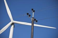 De bladen van de windmolen en elektrische lijnen Stock Foto