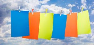 De bladen van gekleurd document, maken wasknijpers vast tegen de hemel Royalty-vrije Stock Foto's