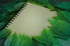 De bladeren en het notitieboekje op houten tuinlijst Uitstekende beeldtoon van de Herfstachtergrond kan gebruikt tekstbericht of  Stock Afbeelding