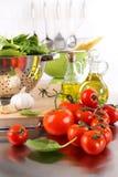 De bladeren van de spinazie in zeef met tomaten Stock Foto's