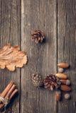 De bladeren van de herfst op houten achtergrond gele de herfstbladeren en eikels op het bord stock afbeeldingen