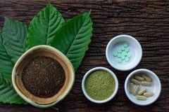 De bladeren van Mitragynaspeciosa kratom met geneeskundeproducten in poeder, capsules en tablet in witte ceramische kom op houten royalty-vrije stock afbeeldingen
