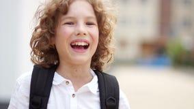 De blauw-eyed jongen verbetert de uitrustingen van de rugzak op zijn schouder en werpt terug krullend haar Sluit omhoog portret stock video
