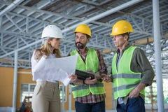 De blauwdruk van de inspecteursholding en het bekijken arbeiders in bouwvakkers royalty-vrije stock foto