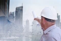 De blauwdrukken van een ingenieursstudie tegen stedelijke achtergrond stock foto's