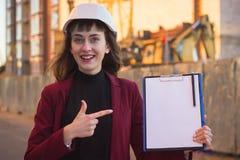 De blauwdrukken van de vrouwenholding, klembord Glimlachende architect in helm bij de bouw stock foto's