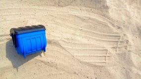 De blauwe afvalstuk speelgoed container ligt op het zand met een exemplaarruimte voor tekst over huisvuilverwijdering, milieubesc royalty-vrije stock afbeeldingen