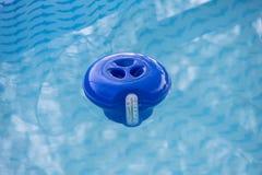 De blauwe automaat van de poolchloor in het water stock afbeeldingen