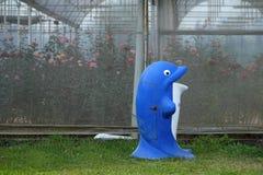 De blauwe bak van het dolfijnafval dichtbij roze tuin stock foto's