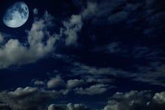 De blauwe bewolkte hemel van de nacht met sterren en een maan Royalty-vrije Stock Foto