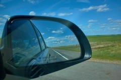 De blauwe bewolkte zonsondergang van het hemellandschap denkt in spiegel van auto na stock foto's