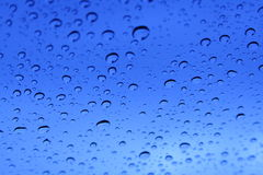 De blauwe Dalingen van de Regen op een Venster Stock Afbeeldingen