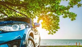 De blauwe die auto van sportsuv door het tropische overzees onder parapluboom wordt geparkeerd De zomervakantie bij het strand De stock afbeeldingen