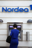 De blauwe geklede vrouw maakt een withdravel van Nordea punt innen Stock Fotografie