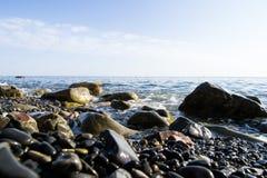 De blauwe golven die tegen de stenen verpletteren die op de kust van de Zwarte Zee liggen royalty-vrije stock afbeeldingen