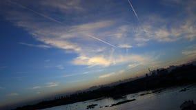 De blauwe hemel in een ochtend, zonstijging, ziet vliegtuiglijn, rivier Stock Foto