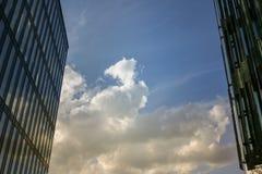 De blauwe hemel met witte wolken tussen twee grote moderne gebouwen Stock Fotografie