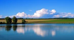 De blauwe hemel van het landschapsmeer en bezinningen van wolken in water Stock Afbeelding