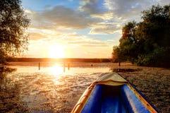 De blauwe kajak tegen de zonsondergang zal stroomafwaarts varen stock afbeeldingen