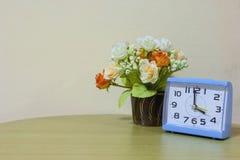 De blauwe klok van het close-upalarm, 4 uur met bloem op muurachtergrond stock foto's