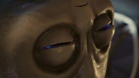 De blauwe lichten zijn opvlammend binnen ogen van vreemd hoofd in laboratorium, close-up stock videobeelden