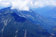 De blauwe majestueuze bergen en de bezinningen van reusachtige wolken op de pieken Royalty-vrije Stock Foto's