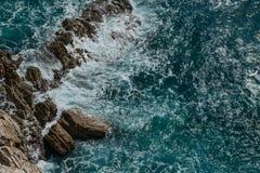 De blauwe overzeese golven slaan tegen de kustrotsen royalty-vrije stock afbeeldingen