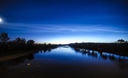 De blauwe riviernacht speelt wolkenmaan mee Stock Foto