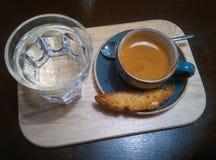 De blauwe schotel en de koffie vormen op een houten dienblad en een glas water tot een kom Stock Fotografie