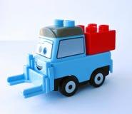 De blauwe stuk speelgoed vrachtwagen met het rode blok Stock Foto's