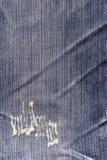 De blauwe textuur van Jean met een gat en draden het tonen Stock Foto