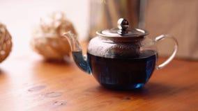 De blauwe thee van de Vlindererwt van bloemen Clitoria op de lijst in de koffie Een bloemen, exotische, blauwe Thaise thee, wat h