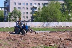 De blauwe tractorwerken aangaande geschermde bouwwerf Stock Afbeeldingen