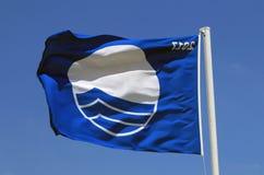 De blauwe vlag vliegt op het strand Stock Afbeeldingen