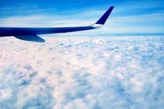De blauwe vleugel die van een groot vliegtuig, tijdens de witte ochtend vliegen betrekt, bij hoge hoogte boven de grond, tegen de royalty-vrije stock afbeelding