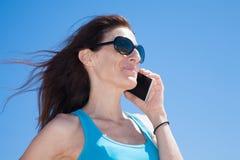De blauwe vrouw die van het overhemdsprofiel op mobiele telefoon spreken Stock Fotografie