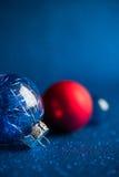 De blauwe, zilveren en rode Kerstmisornamenten op donkerblauw schitteren achtergrond met ruimte voor tekst Stock Fotografie
