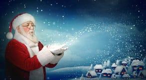 De blazende sneeuw van Santa Claus aan weinig stad Royalty-vrije Stock Foto