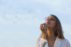 De blazende zeepbels van het meisje stock foto