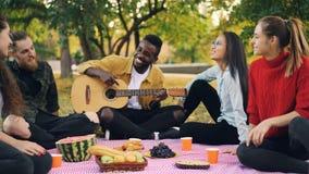 De blije Afrikaanse Amerikaanse kerel speelt de gitaar terwijl zijn vrienden zitting rond hem op picknick in park zingen stock videobeelden