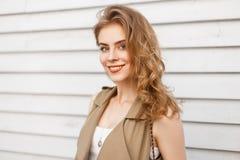 De blije charmante jonge vrouw met natuurlijke samenstelling met krullend blond haar in een modieus vest glimlacht stock foto