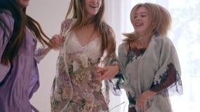 De blije emoties, gelukkige jonge vrouwen springt pret op bed tijdens de pyjamapartij in langzame motie stock footage