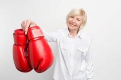 De blije en aardige oude vrouw houdt bokshandschoenen in haar rechts en glimlachend Zij heeft wat in haar pensionering te doen stock fotografie